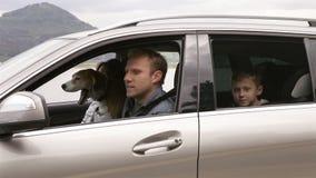 Madre, padre, perro del hijo y del beagle que se sienta en el coche, correas de sujeción y movimiento apagado al viaje
