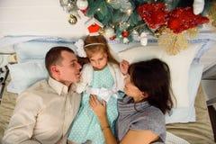 Madre, padre y bebé divirtiéndose en dormitorio Gente que se relaja en casa Concepto de Navidad de las vacaciones de invierno y d imagenes de archivo