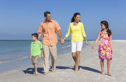 Madre, padre y familia de los niños que recorre en la playa Foto de archivo libre de regalías