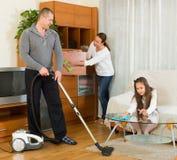 Madre, padre y muchacha haciendo la limpieza general Imágenes de archivo libres de regalías