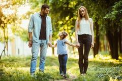 Madre, padre y niña caminando en parque del verano y divirtiéndose Imagen de archivo libre de regalías