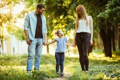 Madre, padre y niña caminando en parque del verano y divirtiéndose Imágenes de archivo libres de regalías
