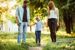 Madre, padre y niña caminando en parque del verano y divirtiéndose Foto de archivo