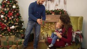 Madre, padre y pequeño bebé sentándose cerca del árbol de navidad adornado Sirva tomar la pequeña actual caja y da a metrajes