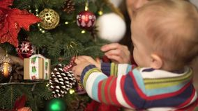 Madre, padre y pequeño bebé sentándose cerca del primer adornado del árbol de navidad Niño de la tenencia del hombre cerca del ár almacen de metraje de vídeo