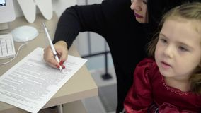 Madre paziente con i documenti di firma del bambino in clinica stock footage