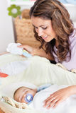 Madre pensativa que oscila su mentira del bebé Foto de archivo