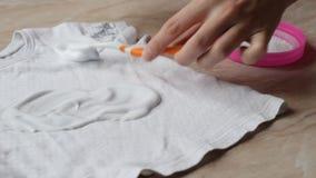 Madre per liberare le macchie sui vestiti dei bambini dalle caramelle con l'aiuto dello smacchiatore e del detersivo, primo piano video d archivio
