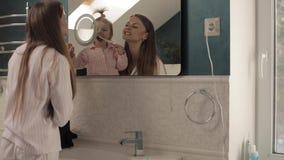 Madre preciosa con pocos dientes de cepillado de la familia en cuarto de baño metrajes