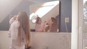 Madre preciosa con pocos dientes de cepillado de la familia en cuarto de baño almacen de metraje de vídeo