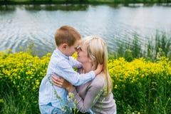 Madre preciosa que besa a su hijo en prado del verano foto de archivo