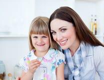 Madre preoccupantesi e la sua figlia che mangiano le verdure Immagini Stock Libere da Diritti