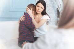 Madre preocupante que calma a su hijo en oficina del psicólogo Imágenes de archivo libres de regalías