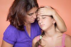 Madre preocupante que toma la temperatura de su hija enferma Fotos de archivo