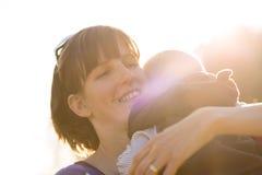 Madre protectora joven feliz que abraza cariñosamente a su bebé Imágenes de archivo libres de regalías