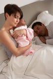 Madre que abraza al bebé recién nacido en cama imagen de archivo libre de regalías