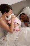 Madre que abraza al bebé recién nacido en cama Imagenes de archivo