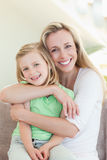Madre que abraza a su hija en el sofá Imágenes de archivo libres de regalías