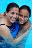 Madre que abraza a su hija en la piscina.