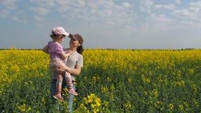 Madre que abraza a su hija en naturaleza Mujer con la niña en campo amarillo Una familia feliz metrajes