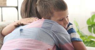 Madre que abraza a su hijo en casa almacen de video