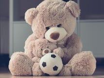 Madre que abraza su oso de peluche del hijo con la bola imagen de archivo