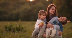 Madre que abraza a sus dos hijos en la puesta del sol en el campo Mamá feliz de amor de los niños almacen de video