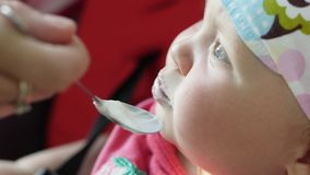 Madre que alimenta a su bebé con una cuchara metrajes