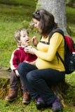 Madre que alimenta a su muchacho afuera en bosque Fotografía de archivo