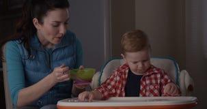 Madre que alimenta su muchacho del niño con las gachas de avena para el desayuno y al bebé que come la comida almacen de video