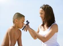 Madre que aplica la crema del sol en niño pequeño Imagen de archivo
