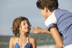Madre que aplica la protección solar a la hija en la playa Imagen de archivo libre de regalías