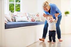 Madre que ayuda al hijo joven como él aprende caminar foto de archivo