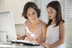 Madre que ayuda a la hija al usar el ordenador y la calculadora Imágenes de archivo libres de regalías