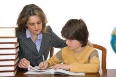 Madre que ayuda a su niño con la preparación Imágenes de archivo libres de regalías