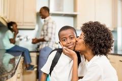 Madre que besa al hijo en la cocina Fotos de archivo libres de regalías