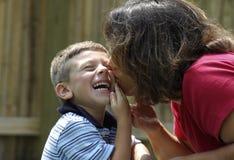 Madre que besa al niño Imagenes de archivo