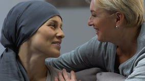 Madre que besa a la hija de amor con el cáncer, apoyando durante la quimioterapia metrajes