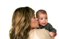 Madre que besa a su bebé fotografía de archivo