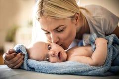 Madre que besa a su bebé que comparte ofertas en casa cierre fotos de archivo libres de regalías