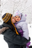 Madre que besa a su hija en invierno Imagen de archivo libre de regalías