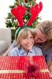 Madre que besa a su hijo en el tiempo de la Navidad Fotografía de archivo