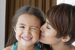 Madre que besa su mejilla del daughter s Fotos de archivo