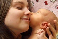 Madre que besa a su niño Fotos de archivo