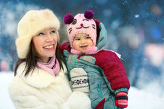 Madre que camina con el bebé en parque del invierno fotos de archivo libres de regalías
