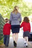 Madre que camina a la escuela con los niños en manera de trabajar Foto de archivo libre de regalías