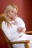 Madre que celebra al bebé recién nacido en silla de oscilación Fotografía de archivo