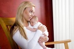 Madre que celebra al bebé recién nacido en silla de oscilación Fotografía de archivo libre de regalías