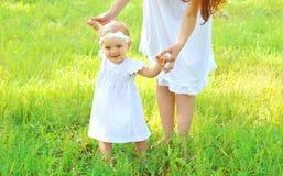 Madre que celebra al bebé de las manos que camina junto Fotografía de archivo