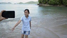 Madre que celebra el teléfono móvil y registración video su hija en la playa metrajes
